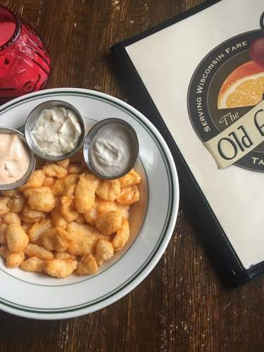 A plate of cheese curds with dipping sauces at The Old Fashioned