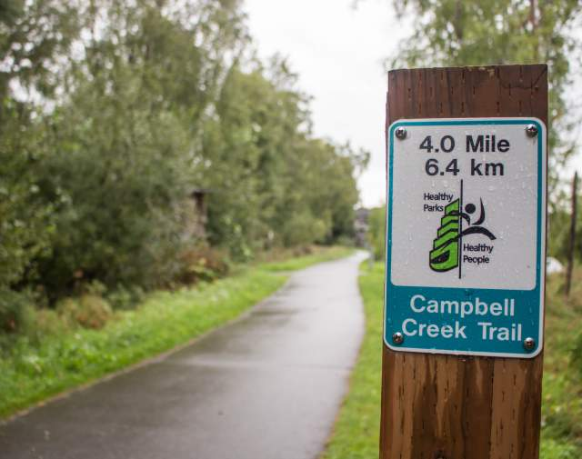 Campbell Creek trail sign with distance and trail name