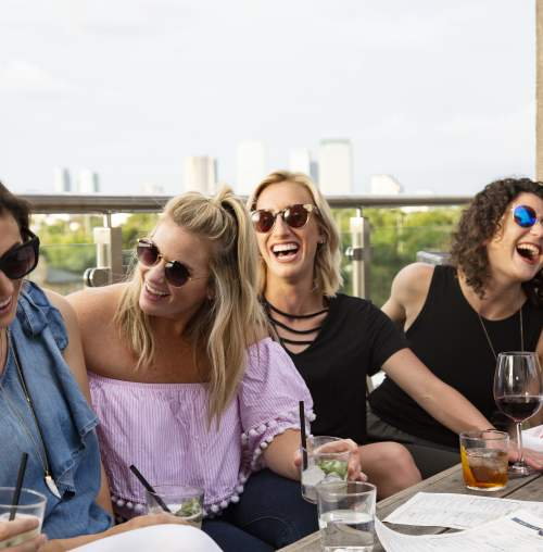 Row of women laughing over drinks