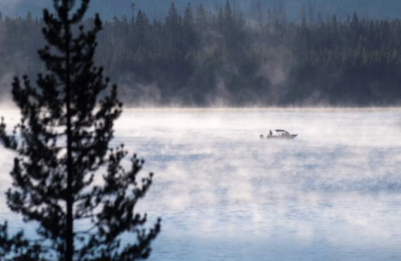 Man sitting in fishing boat at Diamond Lake on a foggy morning.