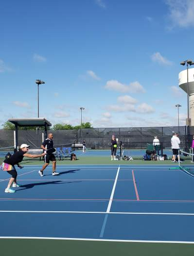 People on the tennis courts at The Courts Tennis Center