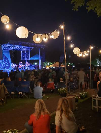 A scene from the Texas Music Revolution festival - crowd with hanging paper lanterns and stage in the background