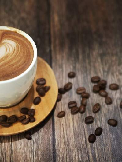 Coffee cup with coffee beans on wooden table top