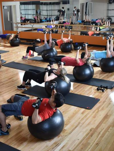 People exercising on yoga balls with weights at the Apex Centre