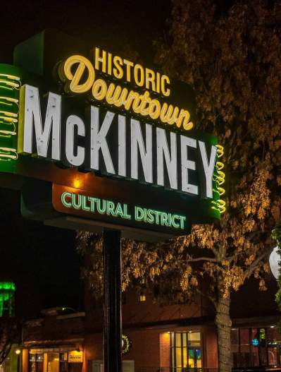 The neon Downtown McKinney Sign at night with the water tower light up green in the background