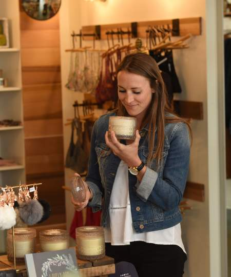 Woman smelling a candle while shopping