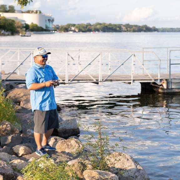 A man fishes on the rocks along Lake Monona