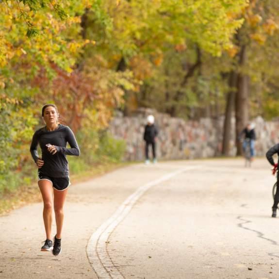 A girl runs along a path through the fall colors