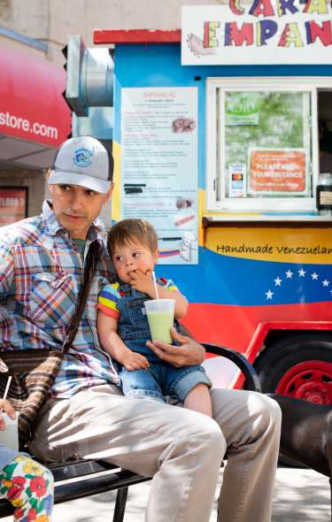 A family sits on a bench enjoying food from one of Madison's many food carts