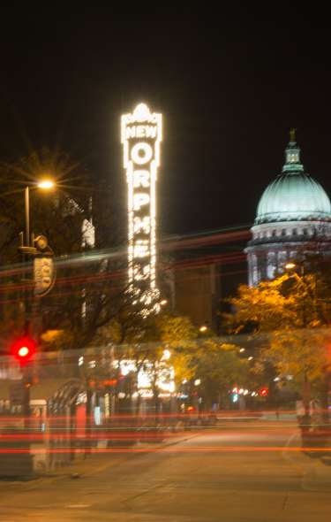 A view of a lit up State Capitol and Orpheum sign at night from State Street