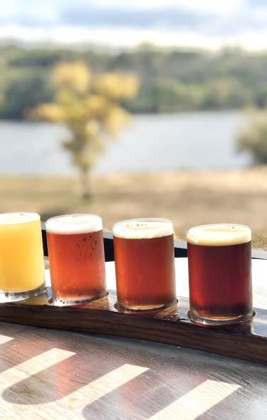 A flight of beer sits on an table outdoors