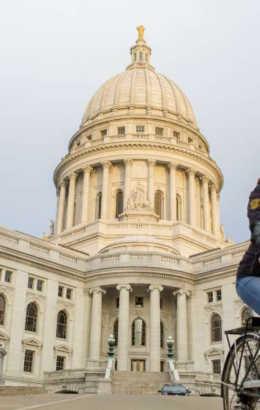 A woman rides her bike in front of the State capitol