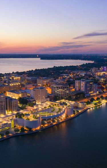 An aerial view of Downtown Madison and the isthmus lit up as dusk approaches