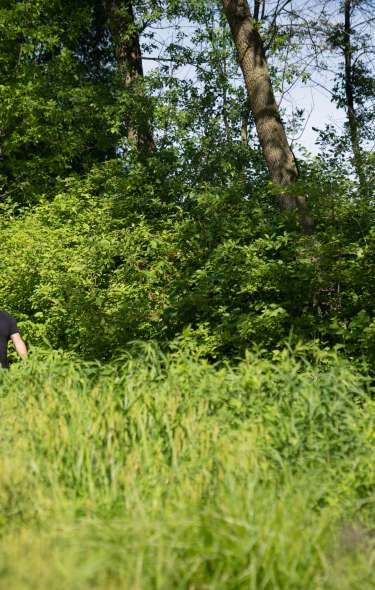 A man and woman hike along a wooded area