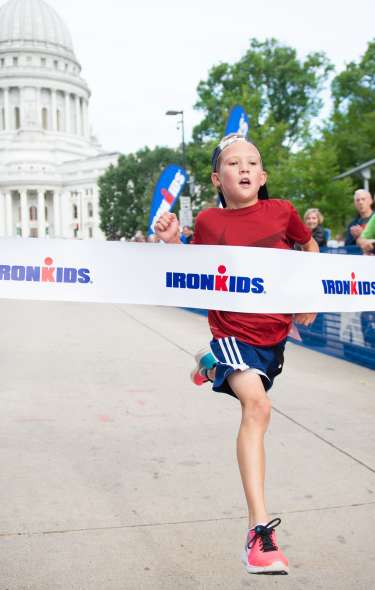A child crosses the IronKids finish line