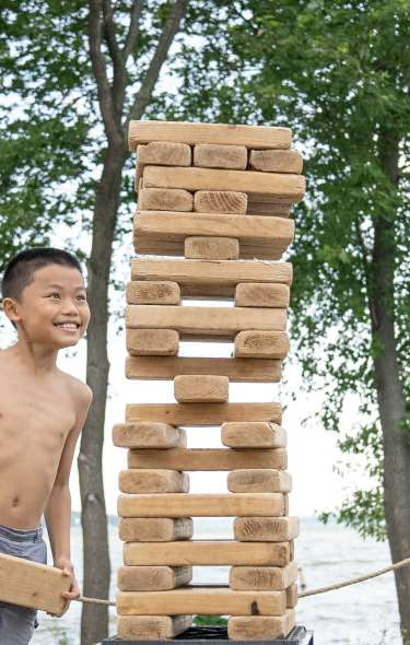 Three boys play a large game of Jenga