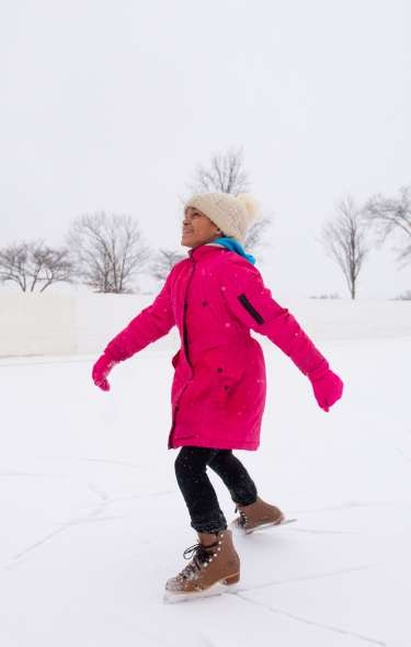 A young girl ice skates on a frozen pond