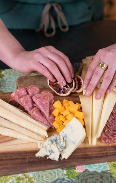 A person crafting a cheese and charcuterie board at Fromagination
