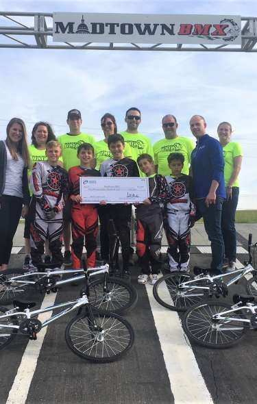 Madtown BMX receives an MASC Youth Grant check