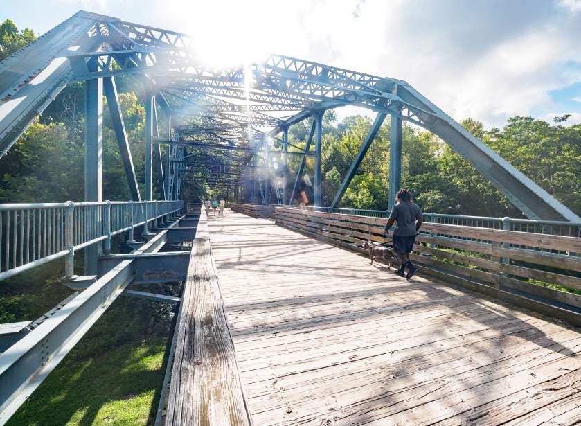 Man Walking Dog Across Bridge