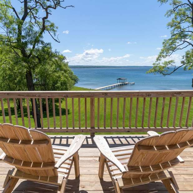 Two Adirondack chairs on deck of vacation rental overlooking lake