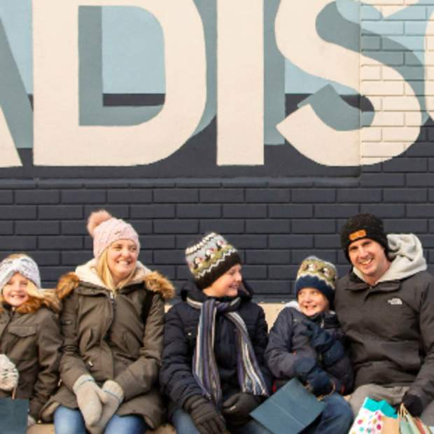 A family poses for a photo in front of a local Madison mural