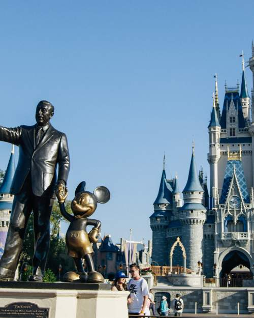 Statue of Walt Disney holding Mickey Mouse's hand in front of the Magic Kingdom castle