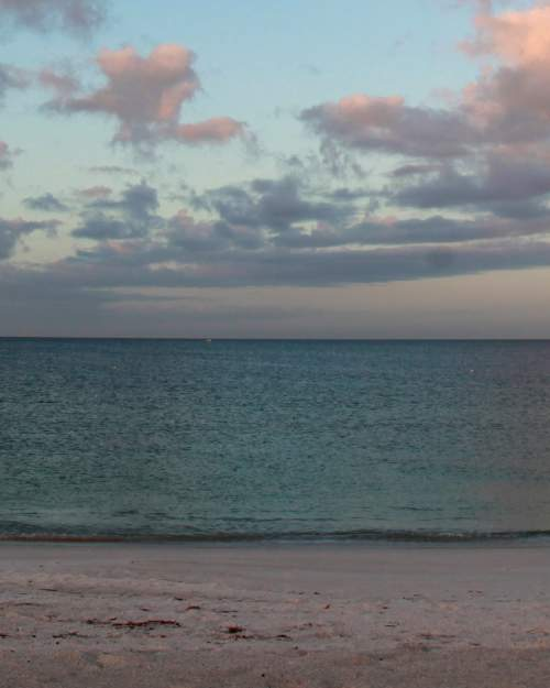 The Gulf of Mexico at sunrise casts a rainbow of hues on Anna Maria Island, where the Bradenton Beach Scenic Highway runs parallel to the water.