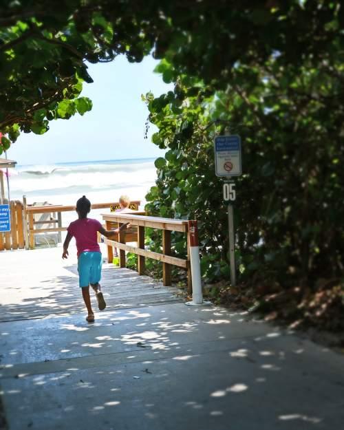 Girl running sea grape arch Delray Beach Atlantic Ocean