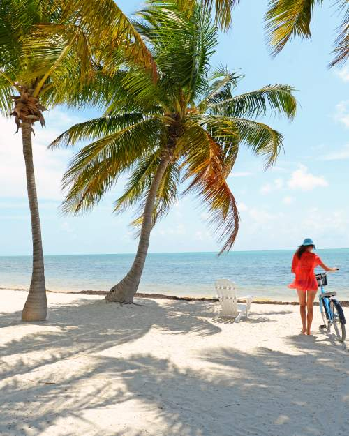Girl riding blue bike on Florida Keys beach with palm trees and white adirondack chair
