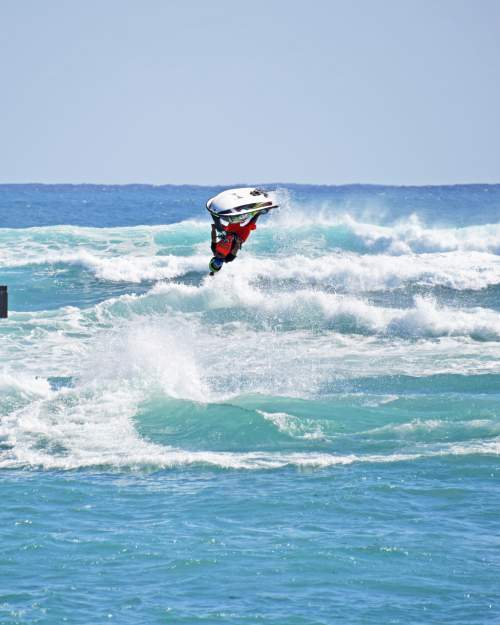 a man doing an aerial 360 flip on a jetski in the ocean waves of palm beach county