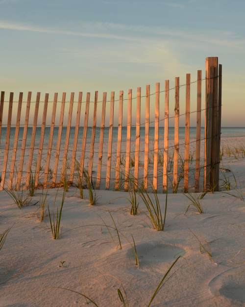 a group of wooden planks strung together to form a fence in the sand at johnson beach
