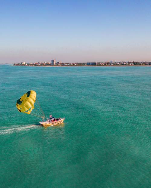 Parasailors lift off from the back of a boat off Siesta Key Beach in Sarasota County.y