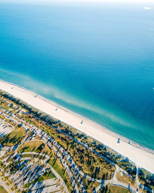 Aerial view of pristine beach with lifeguard towers and blue waters next to road and marina in Miami