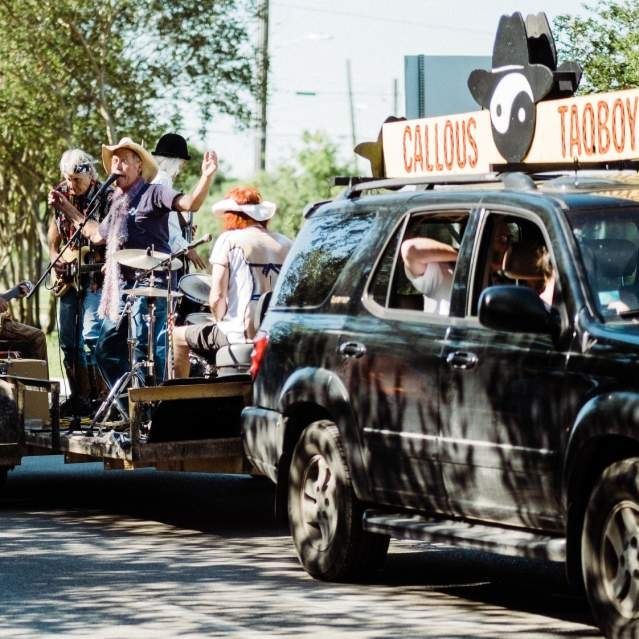 A band playing on a flat bed trailer being pulled by SUV