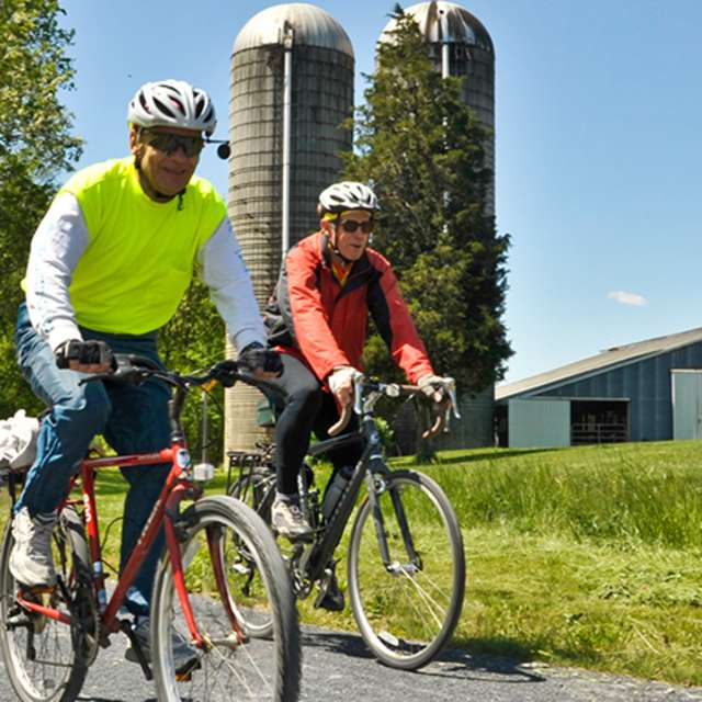Friends ride their bikes along the Cumberland Valley Rail Trail on a clear spring day.