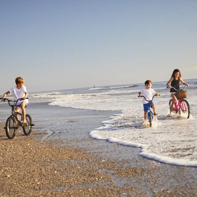 Kids riding bikes on the beach