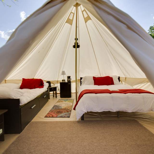 Interior of a luxury glamping tent with two beds at the Shawnee Inn in the Pocono Mountains.