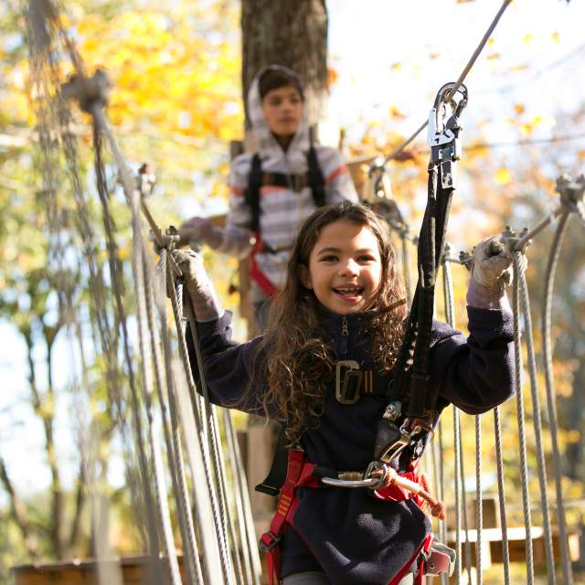 A girl and boy enjoy the high ropes course at an adventure park in the Pocono Mountains