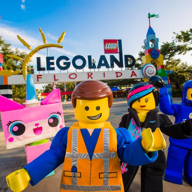 Characters from The Lego Movie stand in front of LEGOLAND Florida Resort Entrance.