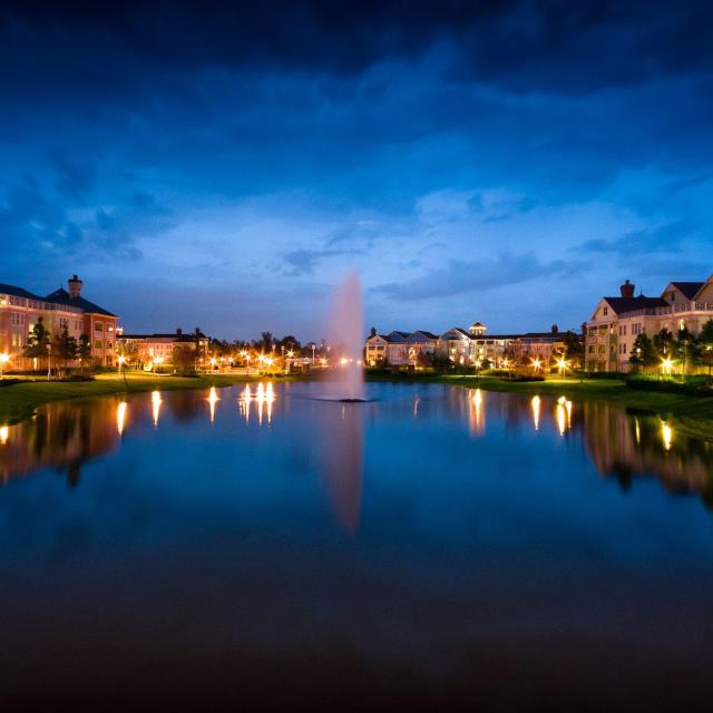 Disney's Saratoga Springs Resort & Spa exterior with lake in foreground at evening