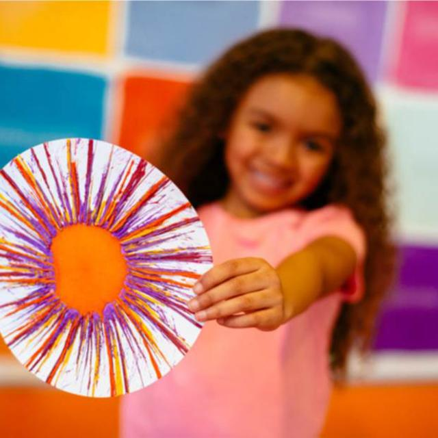 Girl showing off drip art Crayola Experience Orlando