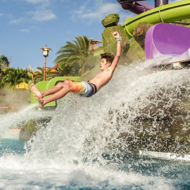 A young man exits the slide drop at Ohno Ohya in Universal's Volcano Bay