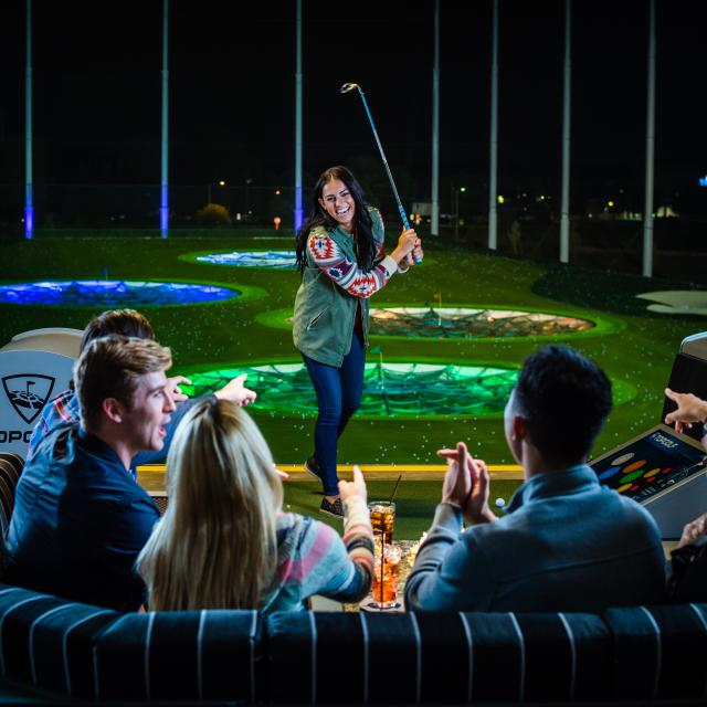 Topgolf group playing golf at night