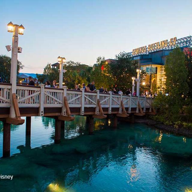 Visitors walk along a bridge at Disney Springs at Sunset.