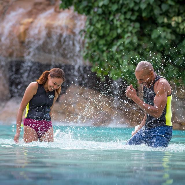 A couple splashing water at each other at Discovery Cove Serenity Bay