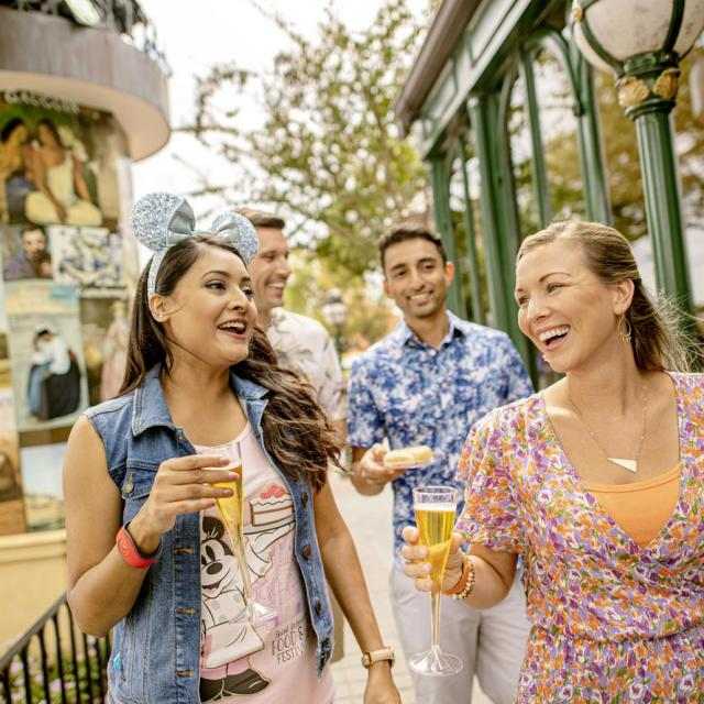 Two couples enjoying drinks at the Epcot Food & Wine Festival