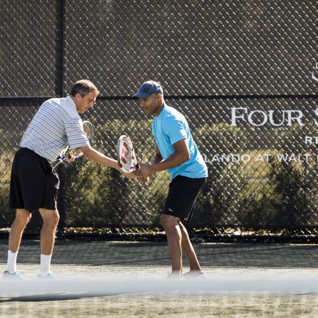 Four Seasons Resort Orlando at Walt Disney World® Resort teaching tennis to adult