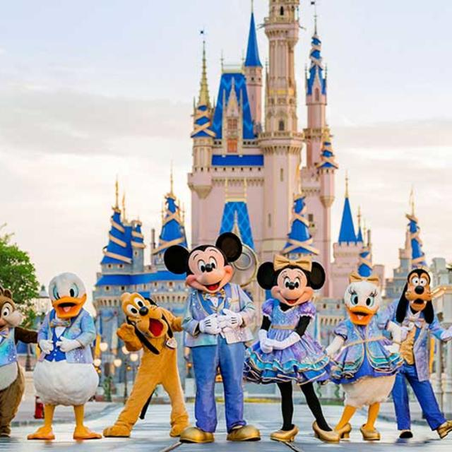 Famous Disney characters pose for a photo in front of Cinderella Castle at Magic Kingdom Park