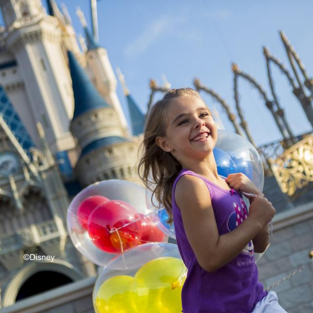 Girl with balloons in front of Cinderella's castle at Walt Disney World Magic Kingdom